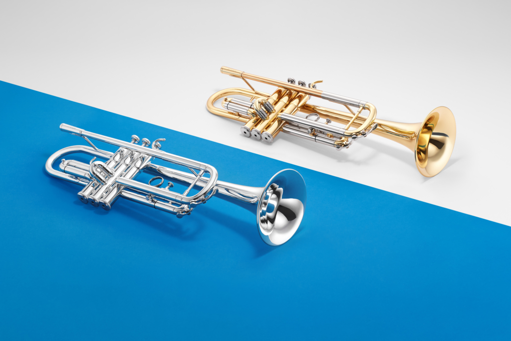 Two trumpets lying on blue and white surfaces